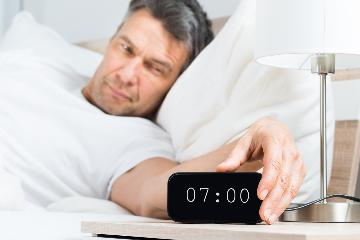 Man waking up to extra-loud alarm clock