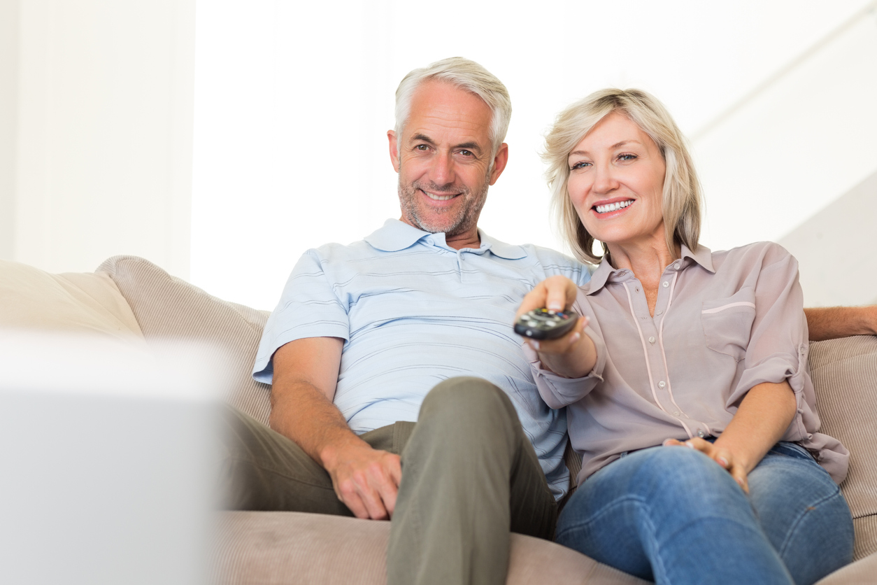 Couple watching tv with hearing aids and tv streamer